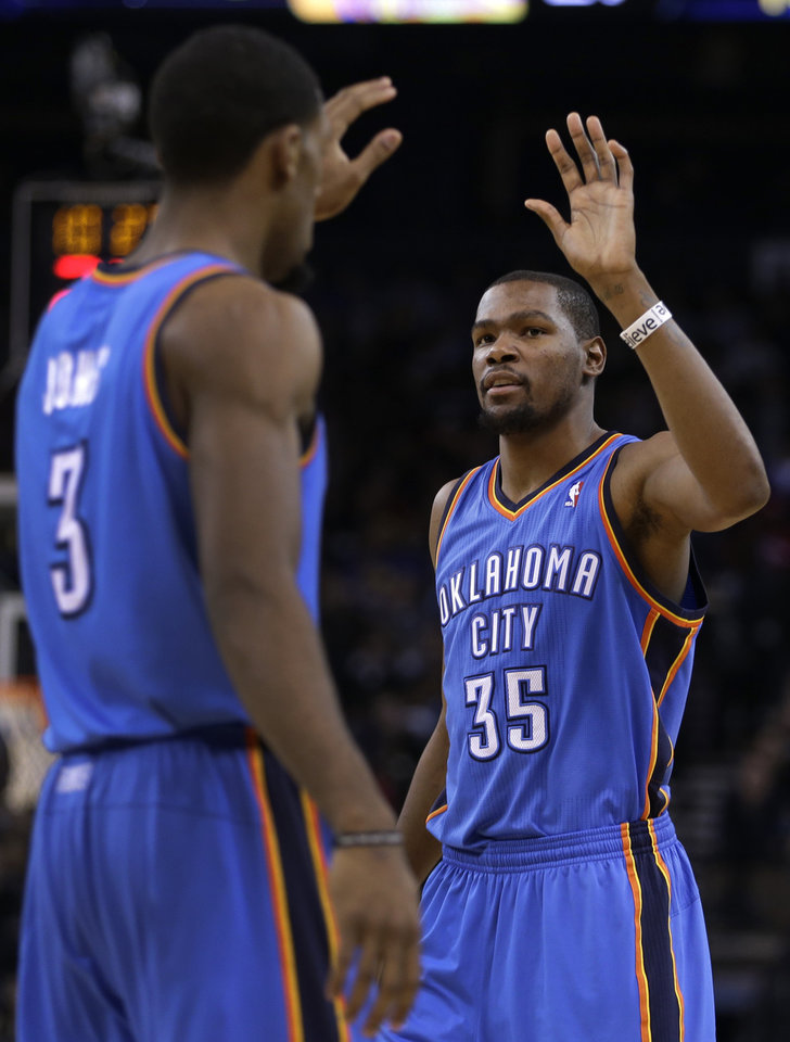 Photo - Oklahoma City Thunder's Kevin Durant, right, celebrates with Perry Jones (3) during the first half of an NBA basketball game against the Golden State Warriors Wednesday, Jan. 22, 2013, in Oakland, Calif. (AP Photo/Ben Margot) ORG XMIT: OAS102