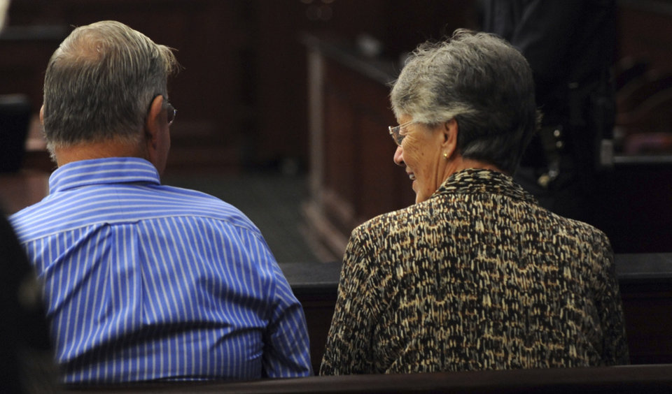 Photo - Phillip and Sandra Dunn, parents of Michael Dunn, talk as they sit in the courtroom as the jury deliberates in the trial of Michael Dunn, Saturday, Feb. 15, 2014 in Jacksonville, Fla. Dunn is charged with fatally shooting 17-year-old Jordan Davis after an argument over loud music outside a Jacksonville convenient store in 2012.  Jurors are entering their fourth day of deliberations, seemingly stuck on whether to convict on some counts but not others. (AP Photo/The Florida Times-Union, Bob Mack, Pool)