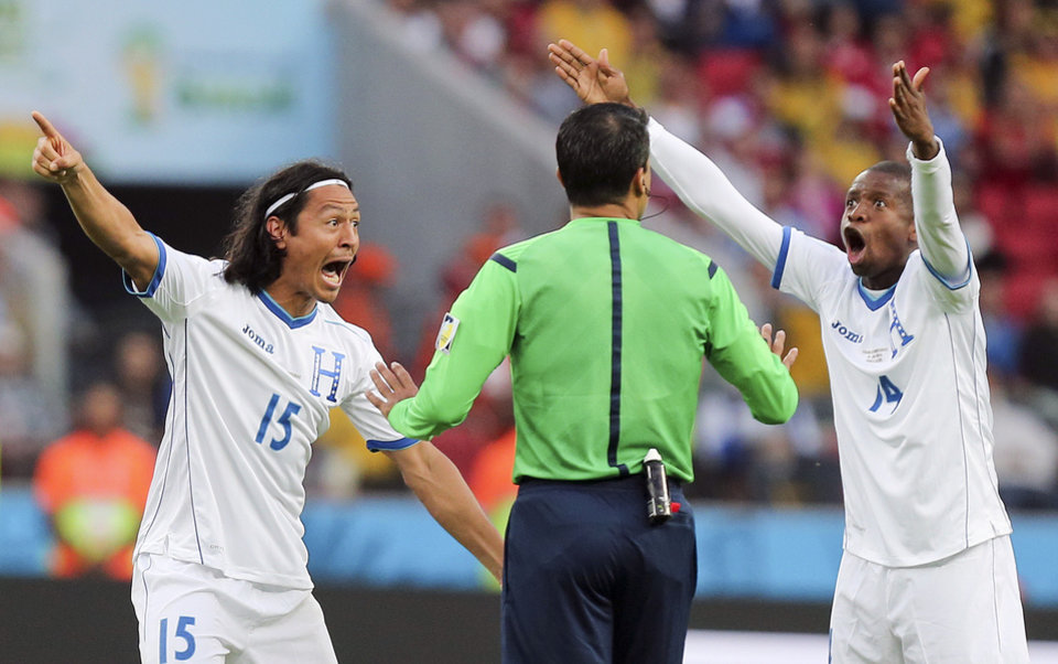 Photo - 10ThingstoSeeSports - Honduras players  Roger Espinoza, left, and Luis Garrido complain to referee Sandro Ricci from Brazil after he awarded a goal to France using goal line technology during the group E World Cup soccer match between France and Honduras at the Estadio Beira-Rio in Porto Alegre, Brazil, Sunday, June 15, 2014. (AP Photo/David Vincent, File)