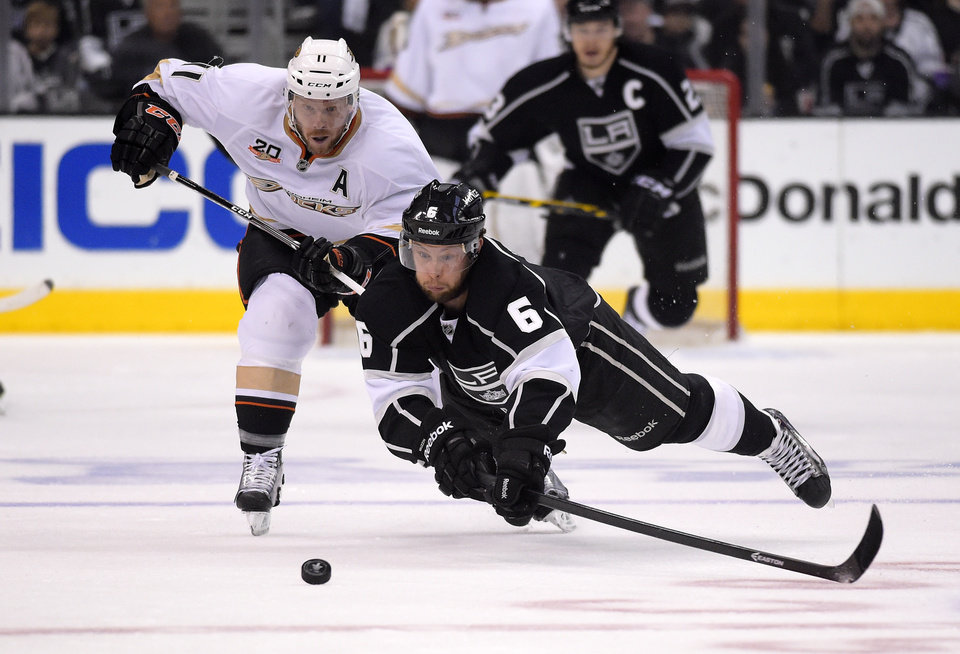 Photo - Los Angeles Kings defenseman Jake Muzzin, right, dives for the puck as Anaheim Ducks center Saku Koivu, of Finland, puts pressure on him during the first period in Game 4 of an NHL hockey second-round Stanley Cup playoff series, Saturday, May 10, 2014, in Los Angeles. (AP Photo/Mark J. Terrill)