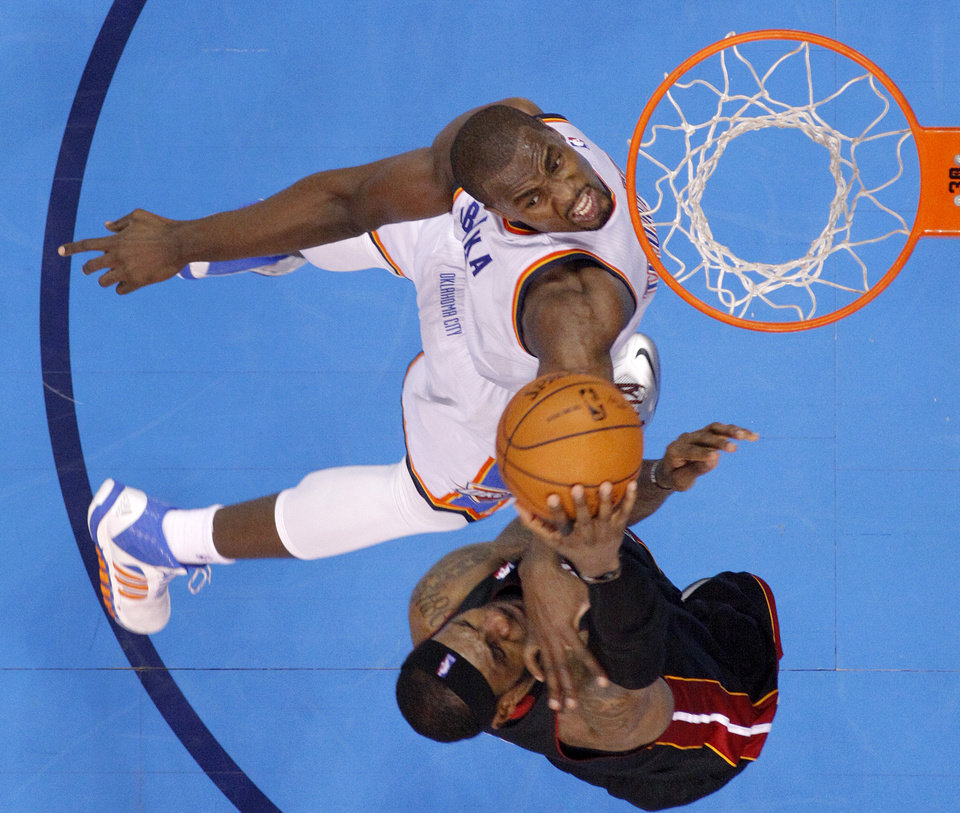 Photo - Oklahoma City's Serge Ibaka (9) guards Miami's LeBron James (6) as he dunks during an NBA basketball game between the Oklahoma City Thunder and the Miami Heat at Chesapeake Energy Arena in Oklahoma City, Thursday, Feb. 20, 2014. James was injured on the play during Oklahoma CIty's 103-81 loss. Photo by Bryan Terry, The Oklahoman