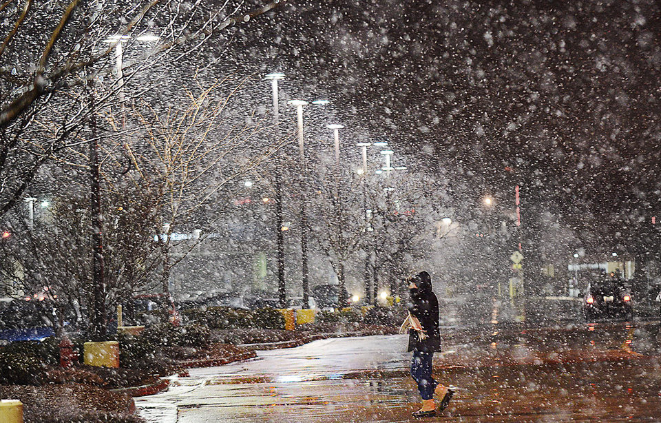 Photo - A pedestrian leaves the Target store off Durham Chapel Hill Boulevard, and walks toward the parking, during a snowy evening, Tuesday, Jan. 21, 2014 in Durham, N.C. (AP Photo/The Herald-Sun, Bernard Thomas)
