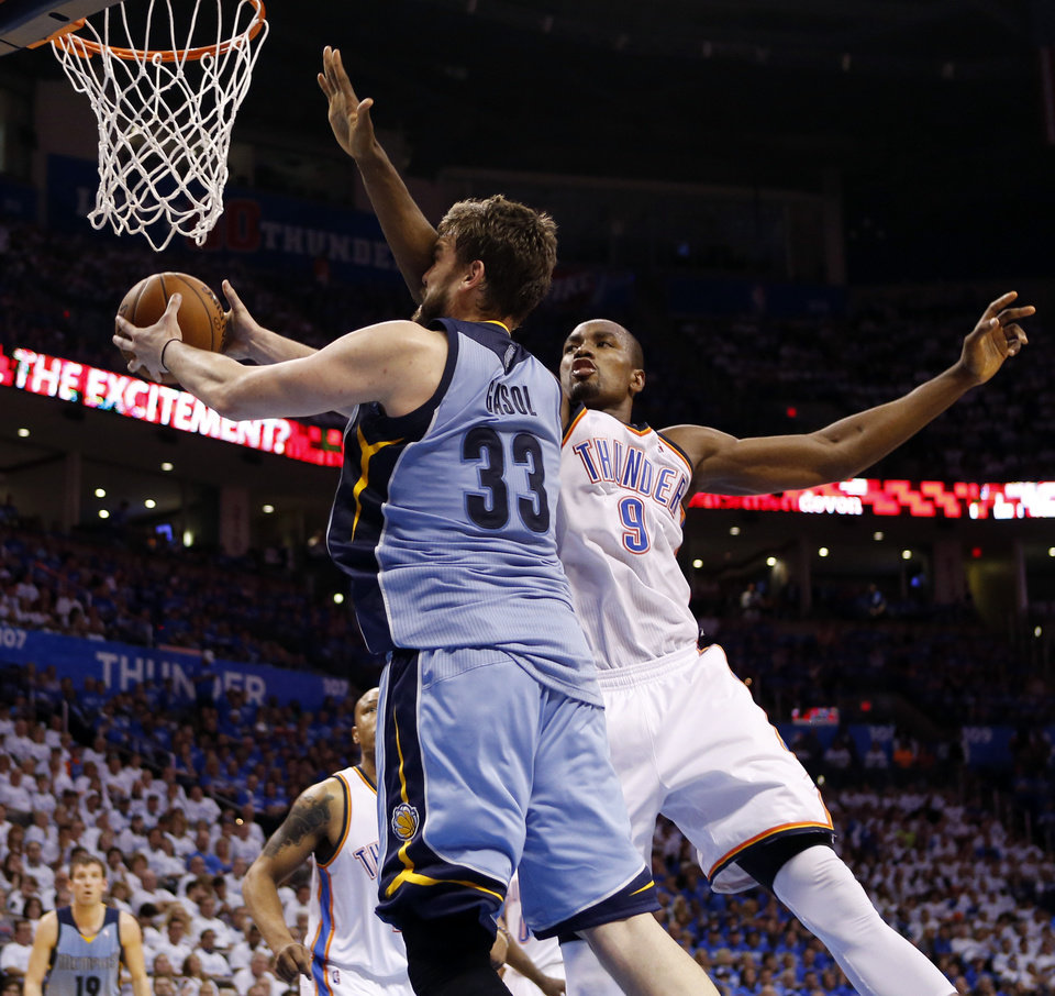 Photo - Oklahoma City's Serge Ibaka (9) defends Memphis' Marc Gasol (33) during Game 2 in the first round of the NBA playoffs between the Oklahoma City Thunder and the Memphis Grizzlies at Chesapeake Energy Arena in Oklahoma City, Monday, April 21, 2014. Memphis won 111-105 in overtime. Photo by Nate Billings, The Oklahoman