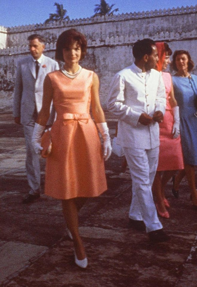 Photo - This handout photo provided by the John F. Kennedy Library and Museum, taken March 17, 1962, shows first lady Jacqueline Kennedy, center, touring the Palace of the Maharajah in Udaipur, India, wearing an apricot silk ziberline dress by Oleg Cassini during a state visit to Udaipur, India. Sure, living in the White House has its perks. But a clothing allowance is not one of them. When Jacqueline Kennedy caught criticism for wearing pricey French fashions, her father-in-law stepped in to defuse the issue. Joseph Kennedy offered to pay her wardrobe bills _ if she used Oleg Cassini, a family friend, as her personal couturier.