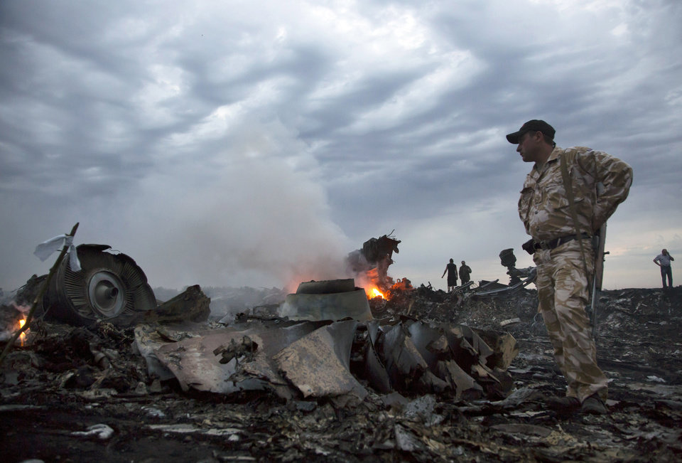 People walk amongst the debris, at the crash site of a passenger plane near the village of Grabovo, Ukraine, Thursday, July 17, 2014. A Ukrainian official said a passenger plane carrying 295 people was shot down Thursday as it flew over the country and plumes of black smoke rose up near a rebel-held village in eastern Ukraine. Malaysia Airlines tweeted that it lost contact with one of its flights as it was traveling from Amsterdam to Kuala Lumpur over Ukrainian airspace. (AP Photo/Dmitry Lovetsky)
