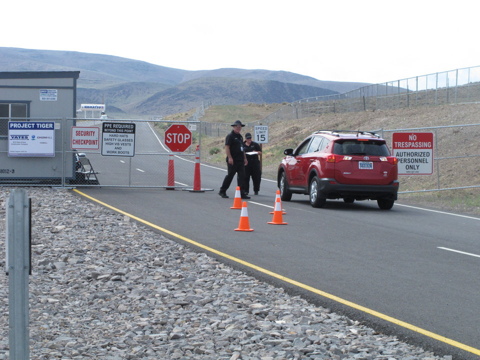 Photo - Security guards stop a car Friday Aug. 1, 2014, at the gate to the site Tahoe Reno Industrial Center about 15 miles east of Reno, Nevada where Tesla Motors has broken ground as one of the possible places to build a $5 billion