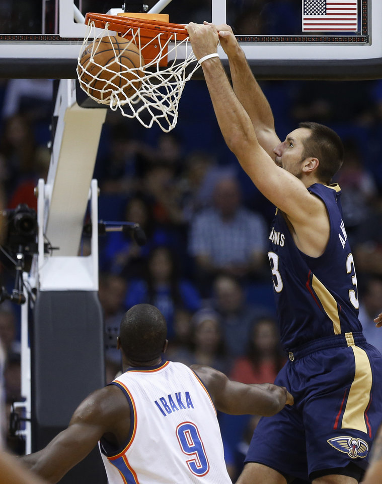 New Orleans Pelicans forward Ryan Anderson (33) dunks in front of Oklahoma City Thunder forward Serge Ibaka (9) in the third quarter of an NBA basketball preseason game in Tulsa, Okla., Thursday, Oct. 17, 2013. New Orleans won 105-102. (AP Photo/Sue Ogrocki) ORG XMIT: OKSO123