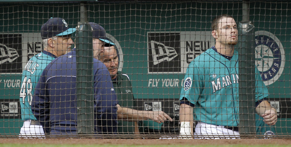 Photo -   Seattle Mariners trainer Rick Griffin, third from left, points to the elbow of Seattle Mariners starting pitcher Blake Beavan, right, after Beavan was hit by a ball in the third inning of a baseball game against the Detroit Tigers, Monday, May 7, 2012, in Seattle. Beavan left the game following the injury. Looking on at left are Mariners pitching coach Carl Willis, left, and bench coach Robby Thompson, second from left. (AP Photo/Ted S. Warren)