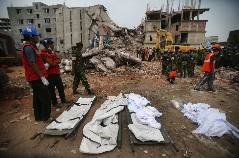 Photo - Stretchers with a body bags are placed on standby while workers toil in the collapsed garment factory building,  Tuesday, April 30, 2013 in Savar, near Dhaka, Bangladesh. Emergency workers hauling large concrete slabs from a collapsed 8-story building said Tuesday they expect to find many dead bodies when they reach the ground floor, indicating the death toll will be far more than the official 386. One estimate said it could be as high as 1,400. The illegally constructed, 8-story Rana Plaza collapsed on the morning of April 24, bringing down the five garment factories inside.(AP Photo/Wong Maye-E)