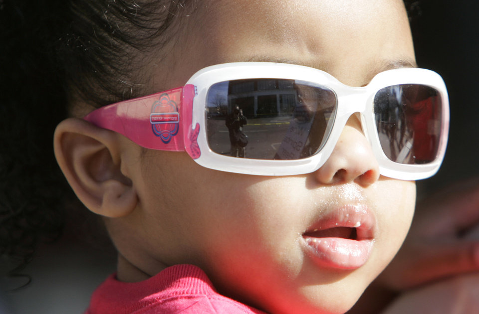 Photo - SUNGLASSES / CHILD  / CHILDREN / KIDS: 2-year-old Alana Robison watches the Martin Luther King Jr. Day Parade in Oklahoma City, Oklahoma January 18, 2010. Photo by Steve Gooch, The Oklahoman ORG XMIT: KOD