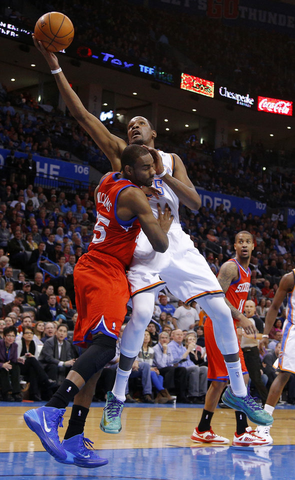 Photo - Oklahoma City's Kevin Durant (35) is fouled by Philadelphia's Elliot Williams (25) during an NBA basketball game between the Oklahoma City Thunder and the Philadelphia 76ers at Chesapeake Energy Arena in Oklahoma City, Tuesday, March 4, 2014. Photo by Bryan Terry, The Oklahoman