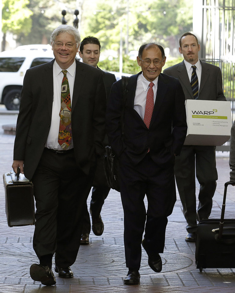 Photo - Apple attorneys Harold McElhinny, left, and William Lee, walk with others to a federal courthouse in San Jose, Calif., Monday, April 28, 2014. Dueling expert witnesses were called back to the stand Monday in a San Jose federal courtroom to discuss whether the ruling in a legal dispute between Apple and Motorola has any effect on the Apple and Samsung trial. (AP Photo/Jeff Chiu)