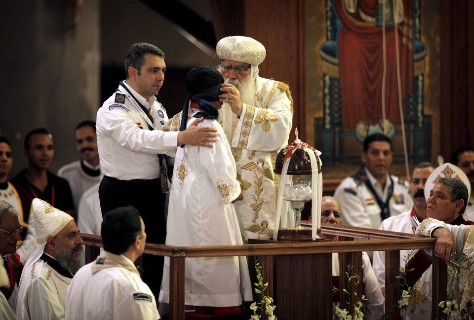 Acting Coptic Pope Pachomios, center, blindfolds the boy elected to draw the name of the next patriarch from a crystal chalice, during the papal election ceremony at the Coptic Cathedral in Cairo, Egypt, Sunday, Nov. 4, 2012. Egypt's ancient Coptic Christian church chose a new pope in an elaborate Sunday ceremony meant to invoke the will of God, in which a blindfolded boy drew the name of the next patriarch from a crystal chalice. Bishop Tawadros will be ordained Nov. 18 as Pope Tawadros II, the spiritual leader of a community that increasingly fears for its future amid the rise of Islamists to power in the wake of the 2011 ouster of longtime authoritarian leader Hosni Mubarak.(AP Photo/Nasser Nasser)
