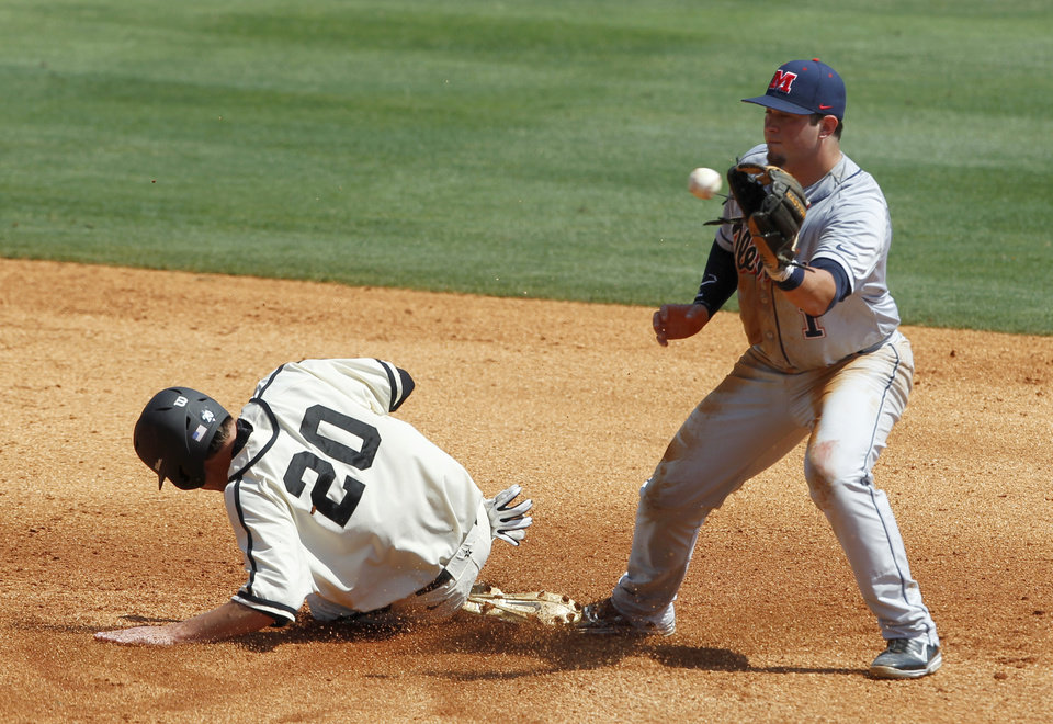 Photo - Vanderbilt's Bryan Reynolds (20) beats the throw to Mississippi's Preston Overbey (1) as he slides into second base during the third inning at the Southeastern Conference NCAA college baseball tournament on Thursday, May 22, 2014, in Hoover, Ala. (AP Photo/Butch Dill)