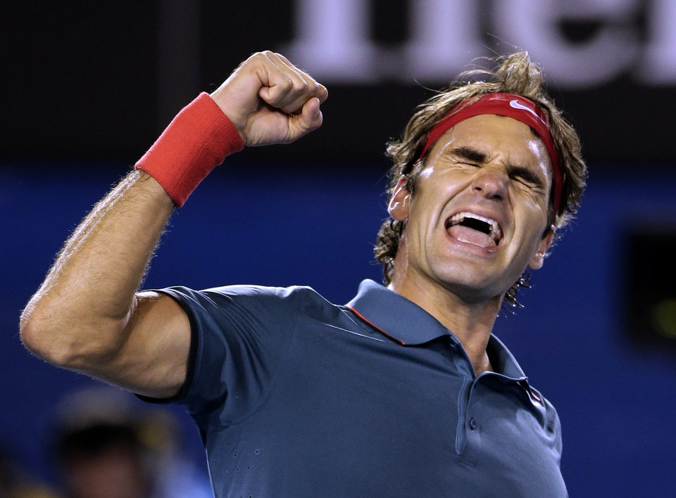 Photo - Roger Federer of Switzerland celebrates after defeating Andy Murray of Britain during their quarterfinal at the Australian Open tennis championship in Melbourne, Australia, Wednesday, Jan. 22, 2014.(AP Photo/Rick Rycroft)