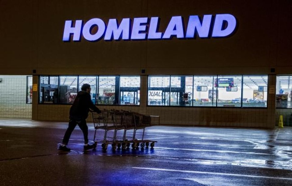 Photo -  A crew member pushes shopping carts in from the parking lot Thursday at the Homeland grocery store at 11241 W Reno in Yukon. Homeland has dedicated the first hour of store operations to senior customers and those who have medical conditions that put them at higher risk from COVID-19.  [Chris Landsberger/The Oklahoman]