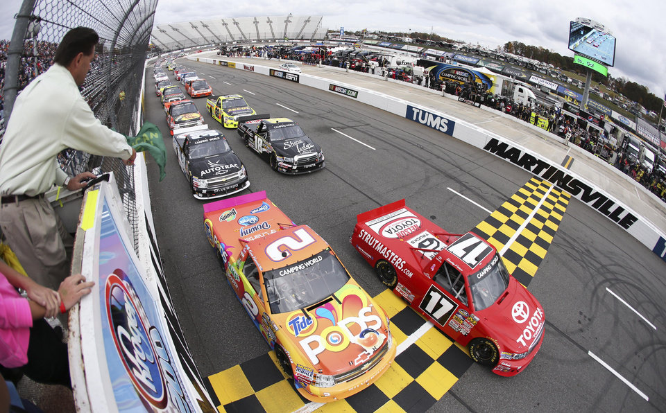 Photo -   Timothy Peters (17) leads Kevin Harvick (2) and the rest of the field past the green flag to start the NASCAR Camping World Truck Series Kroger 200 at Martinsville Speedway on Oct. 27, 2012 in Martinsville, Virginia. (Photo by Streeter Lecka/Getty Images/POOL)