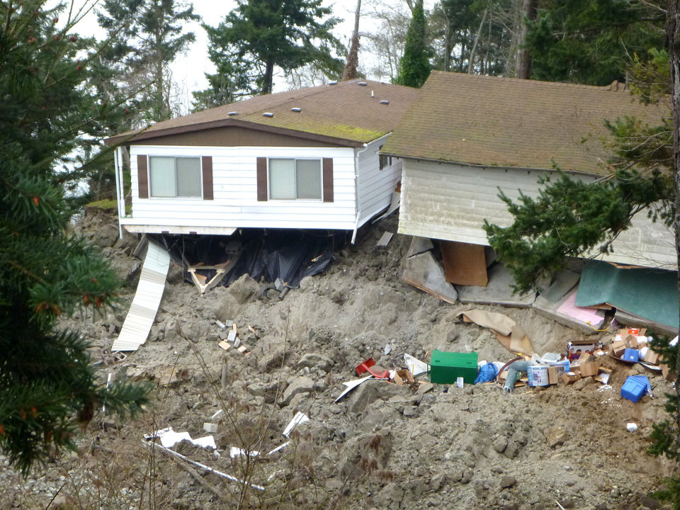 Photo - This March 27, 2013 photo provided by the Washington Dept. of Natural Resources, shows a home  that was damaged by the massive landslide that also isolated or threatened more than 30 others near Coupeville, Wash.  Geologists and engineers are assessing what might happen next after a large landside thundered down the scenic island hillside overlooking Puget Sound.    (AP Photo/Washington Dept. of Natural Resources, Stephen Slaughter)