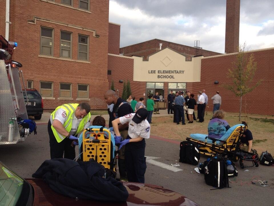 Photo - Paramedics treat a child and an adult outside of Lee Elementary School for an unexplained illness on Monday Nov. 11, 2013. Photo by Graham Brewer / The Oklahoman