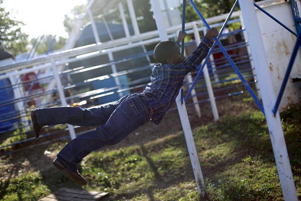 Photo -  DaDa Carter plays on the support poles holding up the announcer's booth as he waits for the Annual Spring Jam Spencer Rodeo in Spencer, Oklahoma to begin on Saturday, May 14, 2011. Photo by John Clanton, The Oklahoman