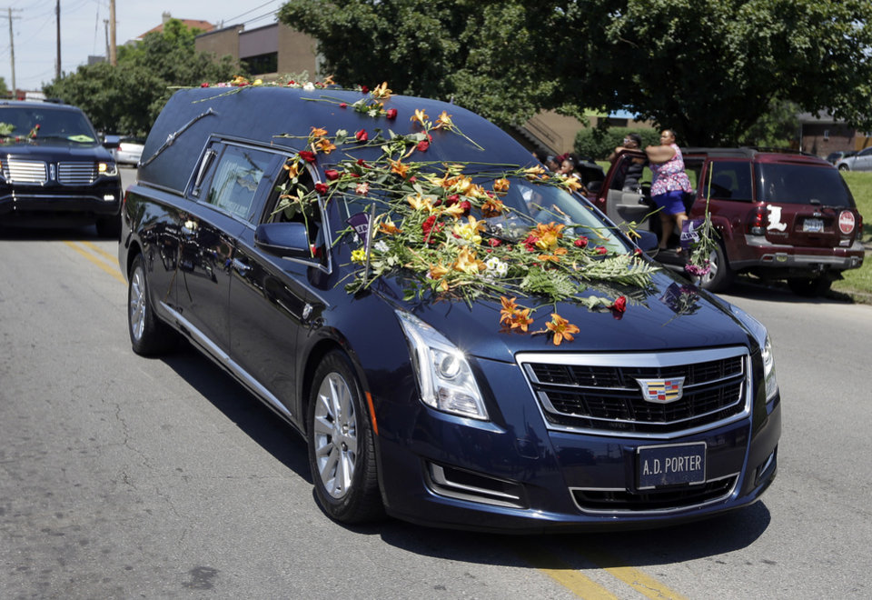 Photo - The flower-covered hearse carrying Muhammad Ali makes its way down Broadway as the funeral procession makes its way to the cemetery in Louisville, Ky. Friday, June 10, 2016. (AP Photo/Michael Conroy)