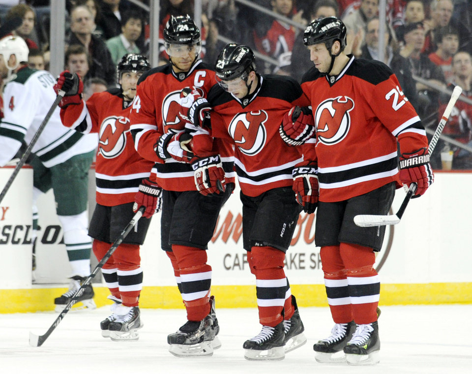 Photo - New Jersey Devils Tim Sestito is helped off the ice by Bryce Salvadore (24) and Ryan Clowe, right, after being elbowed by Minnesota Wild's Nate Prosser during the first period of an NHL hockey game against the Minnesota Wild, Thursday, March 20, 2014, in Newark, N.J. (AP Photo/Bill Kostroun)