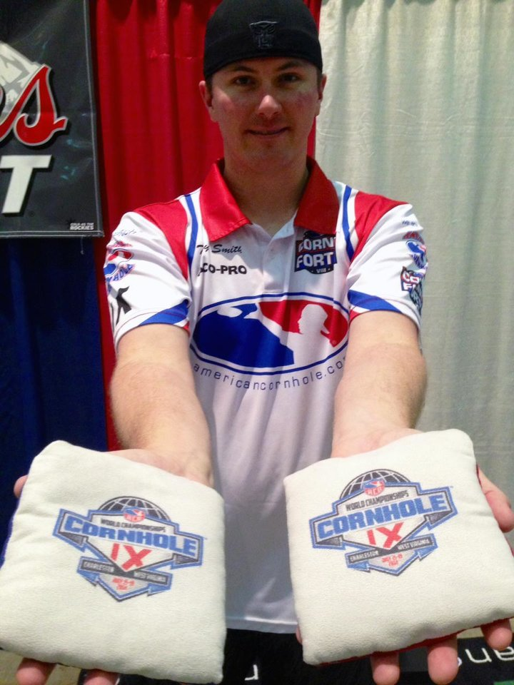Photo - Toby Smith of Blacksburg, Va., poses for a photo as he holds bags used in competition at the World Championships of Cornhole tournament on Friday, July 18, 2014, in Charleston, W. Va. The tournament that crowns winners in singles and doubles events continues through Saturday. (AP Photo/John Raby)