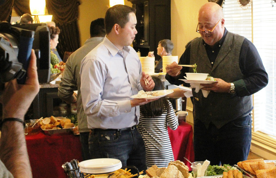 Photo -  Ba Luong, co-owner of Super Cao Nguyen Market, chats with television host and chef Andrew Zimmern, who was in town filming segments for an episode of his