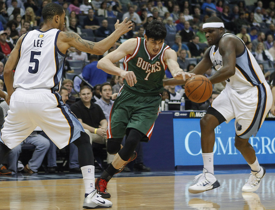 Photo - Milwaukee Bucks forward Ersan Ilyasova (7) drives between Memphis Grizzlies forwards Courtney Lee (5) and Zach Randolph in the first half of an NBA basketball game, Saturday, Feb. 1, 2014, in Memphis, Tenn. (AP Photo/Lance Murphey)