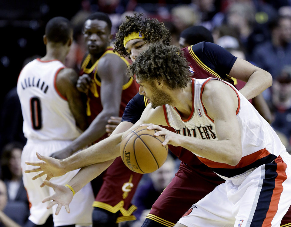 Photo - Cleveland Cavaliers center Anderson Varejao, from Brazil, left, plays tight defense on Portland Trails Blazers center Robin Lopez during the first half of an NBA basketball game in Portland, Ore., Wednesday, Jan. 15, 2014. (AP Photo/Don Ryan)