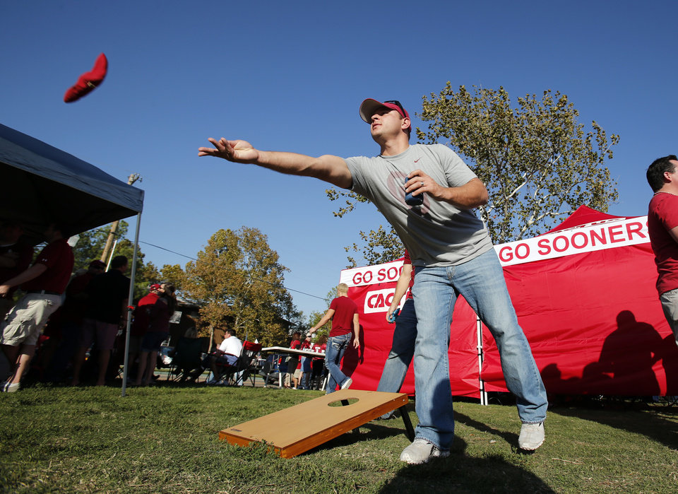 Photo - Josh Deshields, Moore, plays a bean bag toss game as he tailgates with friends before the college football game between the University of Oklahoma Sooners (OU) and the University of Kansas Jayhawks (KU) at Gaylord Family-Oklahoma Memorial Stadium in Norman, Okla., on Saturday, Oct. 20, 2012. Photo by Steve Sisney, The Oklahoman