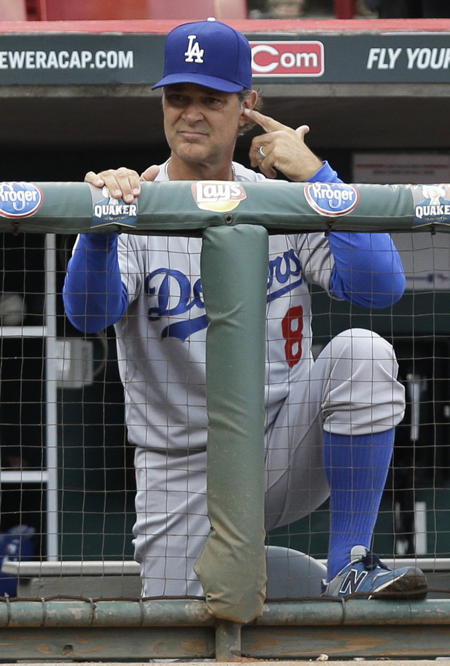Photo - Los Angeles Dodgers manager Don Mattingly gives a sign from the dugout in the first inning of a baseball game against the Cincinnati Reds, Monday, June 9, 2014, in Cincinnati. (AP Photo/Al Behrman)