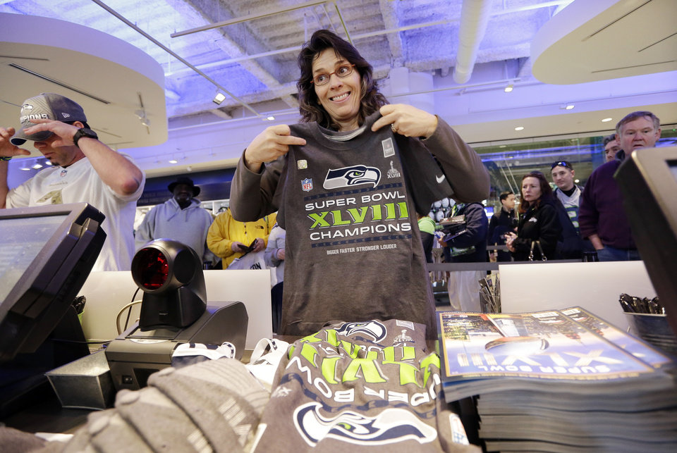 Photo - Julie Keim, of Mukilteo, Wash., looks toward a clerk to check on sizing as she purchases a stack of Seattle Seahawks' Super Bowl championship shirts and caps at the team store, Monday, Feb. 3, 2014, in Seattle. The Seahawks defeated the Denver Broncos on Sunday in the Super Bowl XLVIII NFL football game, 43-8. (AP Photo/Elaine Thompson)