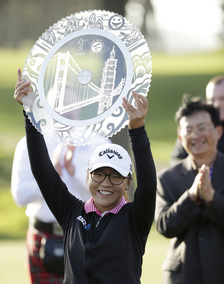 Photo - Lydia Ko of New Zealand holds up her trophy on the 18th green of the Lake Merced Golf Club after winning the Swinging Skirts LPGA Classic golf tournament on Sunday, April 27, 2014, in Daly City, Calif. Ko won the event after shooting a 3-under-par 69 to finish at 12-under-par. (AP Photo/Eric Risberg)
