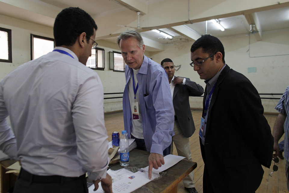 Photo -   U.S. Congressman David Dreier, R-Calif., center, talks to an Egyptian election official inside a polling station during the first day of voting in the country's presidential election on Wednesday, May 23, 2012 in the Zamalek neighborhood of Cairo, Egypt. Determined to end decades of authoritarian rule, millions of Egyptians on Wednesday waited patiently in long lines outside polling stations across the nation to freely chose their first president since last year's ouster of longtime ruler and close U.S. ally Hosni Mubarak. (AP Photo/Maya Alleruzzo)