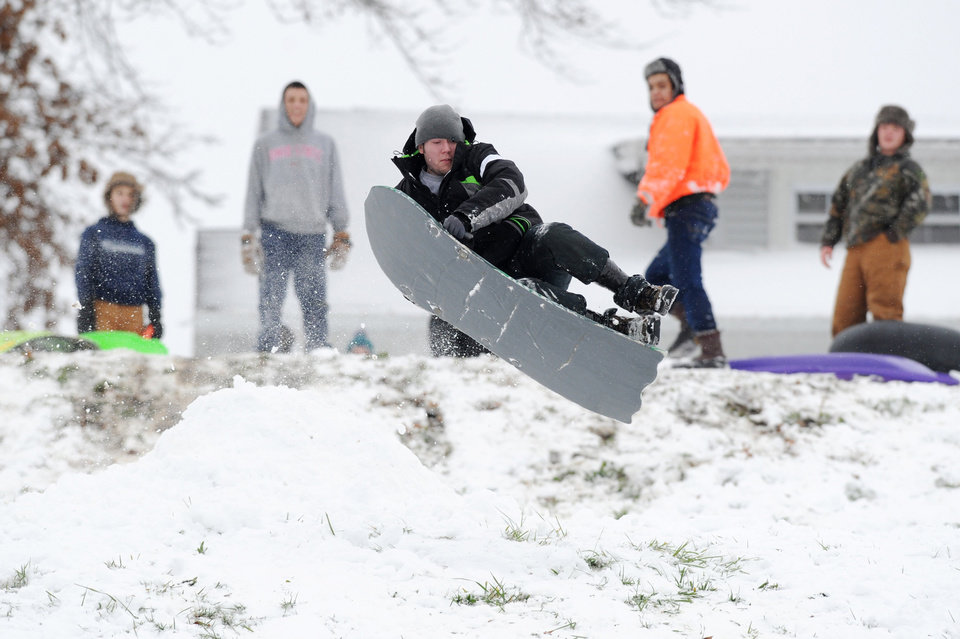 Photo - Kraig Meyer, 20, flies off a homemade snow ramp getting airborne and he and his friends sled down Reitz Hill in Evansville, Ind. on Wednesday afternoon, Dec. 26, 2012. Dozens of people flocked to the hill which was covered in seven inches of snow to enjoy an afternoon of sledding. (AP Photo/The Evansville Courier & Press, Erin McCracken)