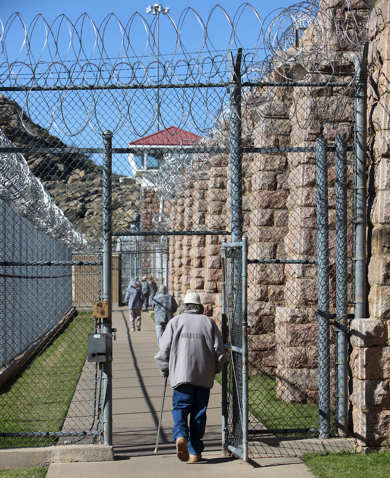 Photo - An inmate with a cane walks through on of the gates at the Oklahoma State Reformatory in Granite, Tuesday, Oklahoma, November 12, 2013. Photo by David McDaniel, The Oklahoman  David McDaniel - The Oklahoman