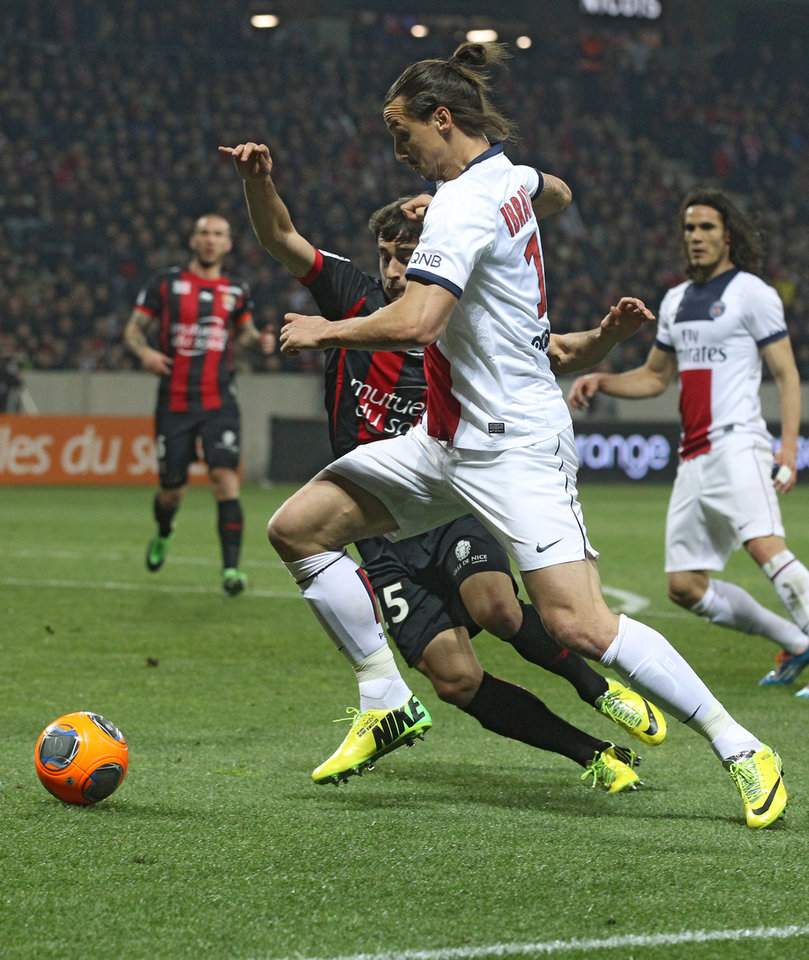 Photo - Paris Saint Germain's Zlatan Ibrahimovic of Sweden, front, challenges Nice's Romain Genevois of France for the ball during their French League One soccer match, in Nice stadium, southeastern France, Friday March 28, 2014. (AP Photo/Lionel Cironneau)