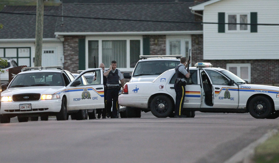 Photo - Royal Canadian Mounted Police officers take cover behind their vehicles in Moncton, New Brunswick, on Wednesday, June 4, 2014. Three police officers were shot dead and two others injured Wednesday in the east coast Canadian province of New Brunswick, officials said, and authorities were searching for a suspect. The RCMP in New Brunswick confirmed on its Twitter feed that three officers were dead and two others had sustained non-life threatening injuries. (AP Photo/The Canadian Press, Viktor Pivovarov, Moncton Times & Transcript)
