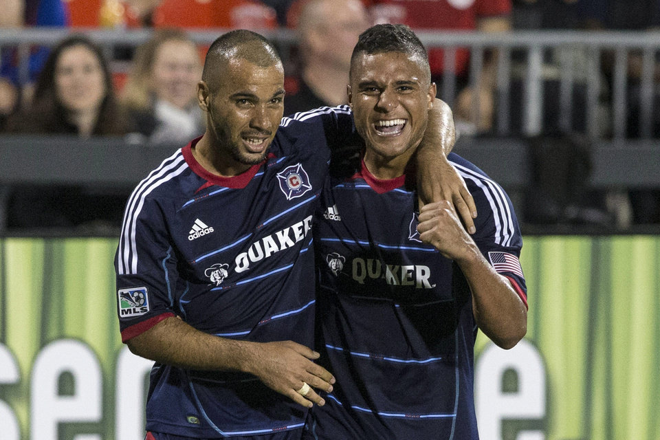 Photo - Chicago Fire's Quincy Amarikwa, right, celebrates with Alex after scoring a late game tying goal against Toronto FC during the second half of a soccer game, Saturday, Aug. 23, 2014 in Toronto. (AP Photo/The Canadian Press, Chris Young)