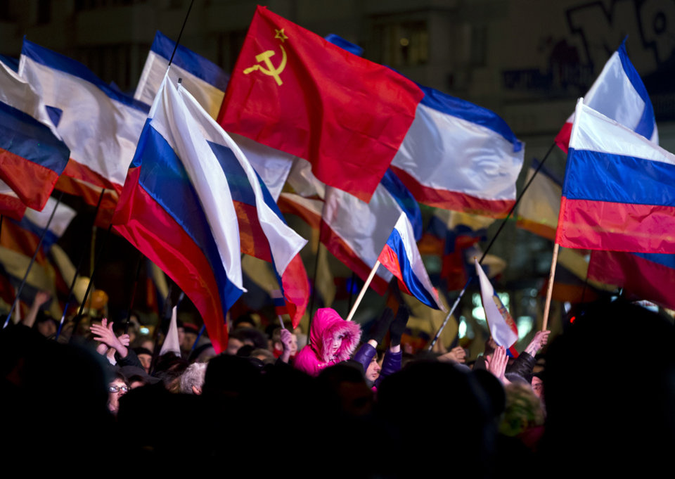 Photo - Pro-Russian people celebrate in Lenin Square, in Simferopol, Ukraine, Sunday, March 16, 2014. Fireworks exploded and Russian flags fluttered above jubilant crowds Sunday after residents in Crimea voted overwhelmingly to secede from Ukraine and join Russia. The United States and Europe condemned the ballot as illegal and destabilizing and were expected to slap sanctions against Russia for it. (AP Photo/Vadim Ghirda)