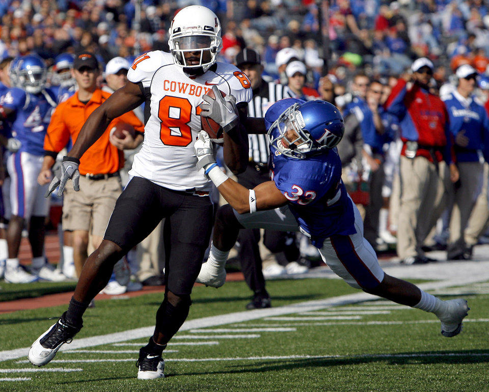 Photo - OKLAHOMA STATE UNIVERSITY: Oklahoma State's Justin Blackmon (81) is brought down by Kansas' Tyler Patmon (33) during the college football game between Oklahoma State (OSU) and Kansas (KU), Saturday, Nov. 20, 2010 at Memorial Stadium in Lawrence, Kan. Photo by Sarah Phipps, The Oklahoman ORG XMIT: KOD
