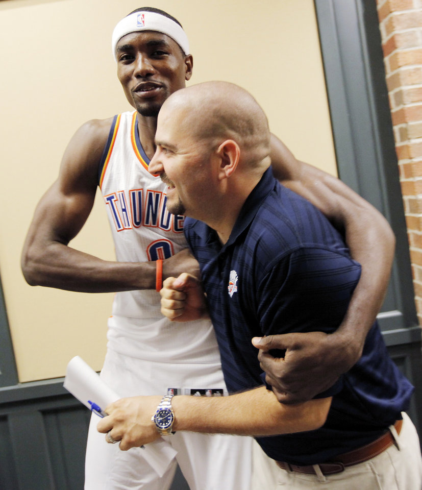 Photo - Thunder player Serge Ibaka jokes with Brian Facchini, director of basketball communications, during media day for the Oklahoma City Thunder at the Ford Center in downtown Oklahoma City, Monday, Sept. 27, 2010. Photo by Nate Billings, The Oklahoman