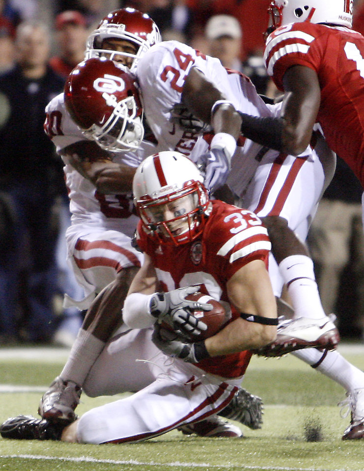 Photo - Nebraska's Matt O'Hanlon (33) pulls down an interception over Oklahoma's Dejuan Miller (24) and Adron Tennell (80) during the second half of the college football game between the University of Oklahoma Sooners (OU) and the University of Nebraska Cornhuskers (NU) on Saturday, Nov. 7, 2009, in Lincoln, Neb.