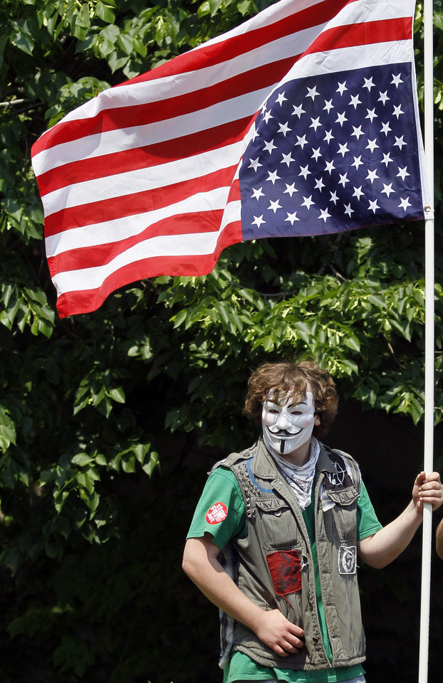 Photo -   A demonstrator stands along the route of a protest march during this weekend's NATO summit in Chicago Sunday, May 20, 2012 in Chicago. (AP Photo/Charles Rex Arbogast)