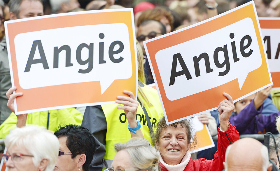 Photo - FILE - In this Monday, Aug. 26, 2013 file photo, supporters of the Christian Democratic Union (CDU) hold placards with the nickname of German Chancellor and CDU leader Angela Merkel at an election campaign event of the CDU  in Ilmenau, central Germany. Ordinary Germans are spooked about the future. Businesses see black clouds on the horizon. And an economy that has been the envy of Europe is already showing cracks, shrinking last quarter under the strain of conflicts in Ukraine and elsewhere. It might seem like enough to put any leader into trouble. But Chancellor Angela Merkel's popularity remains sky-high _ with nobody in sight to touch her. (AP Photo/Jens Meyer, File)