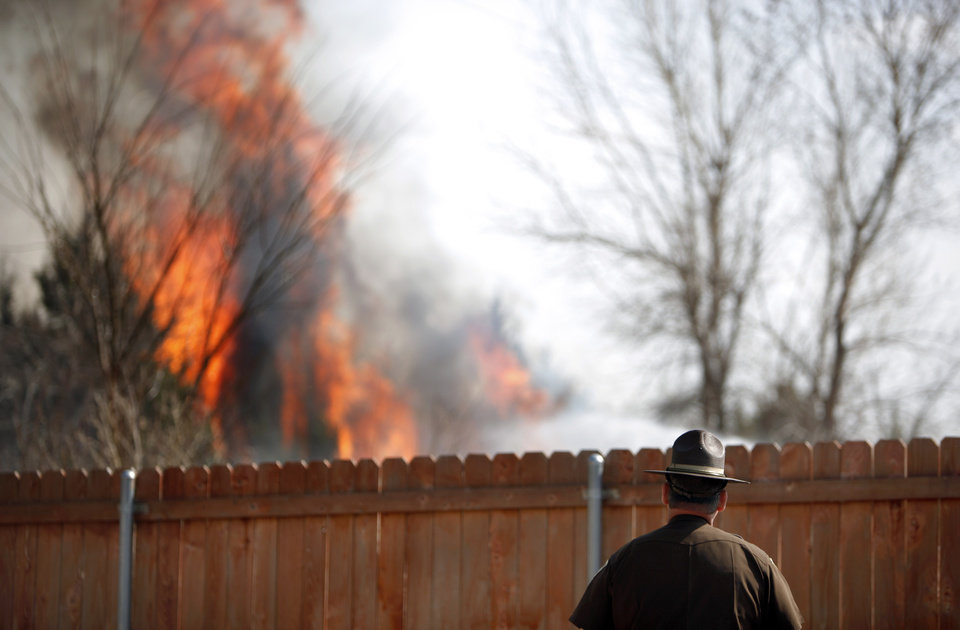 Photo - A highway patrolman watches a grassfire near a neighborhood at South County Line Road and S.W. 29th, Sunday, March 20, 2011, in Mustang, Okla.. Photo by Sarah Phipps, The Oklahoman