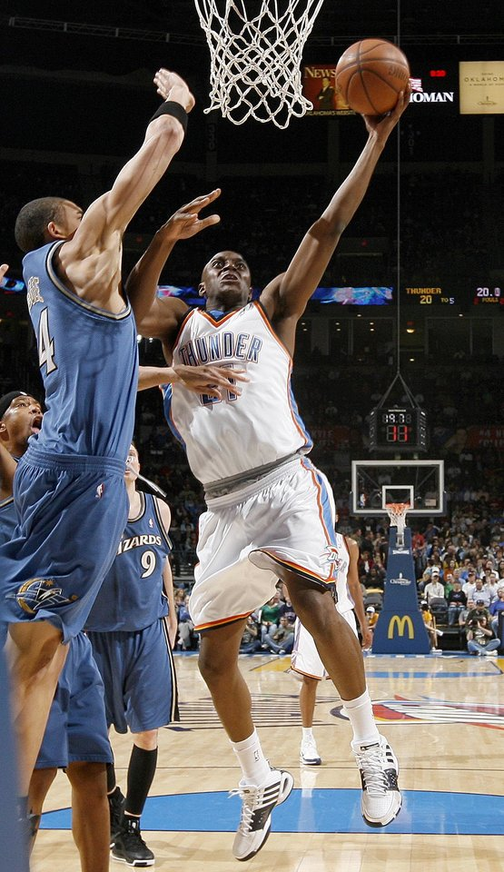 Photo - Oklahoma City's Damien Wilkins goes by Washington's JaVale McGee during the NBA basketball game between the Oklahoma City Thunder and the Washington Wizards at the Ford Center in Oklahoma City, Wed., March 4, 2009. PHOTO BY BRYAN TERRY, THE OKLAHOMAN