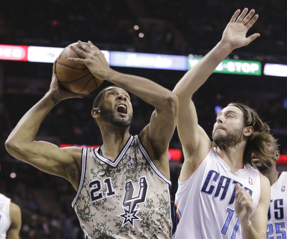 Photo - San Antonio Spurs' Tim Duncan (21) looks to shoot as he is defended by Charlotte Bobcats' Josh McRoberts (11) during the first half of an NBA basketball game, Friday, Feb. 28, 2014, in San Antonio. (AP Photo/Eric Gay)