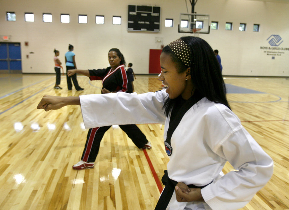 Photo - CHERRY JOHNSON / KARATE: Lauren Johnson, front, and her mother, Cherry, practice together at the Boy & Girls Club on N Western in Oklahoma City Monday, July 27, 2009.  Lauren was diagnosed with cerebral palsy when she was younger, but has overcome the challenges of her disease by placing in several events at the U.S. Open World Martial Arts Championships and becoming a black belt. By Ashley McKee, The Oklahoman ORG XMIT: KOD